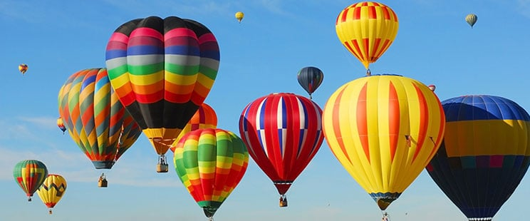 Panoramic view of sixteen hot air balloons of various colors in a blue sky