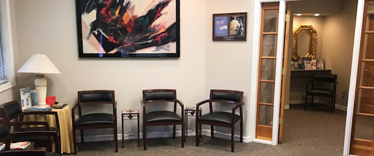 Waiting room in office of Brian K Dennis, DDS with several black chairs and modern art on the wall